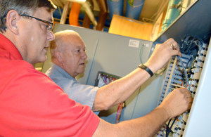 Recommissioning team members Drew Benfield (left) and Ray Lambert test a low-voltage control panel in Engineering Building I.