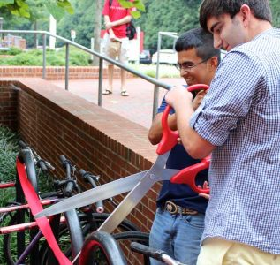 Brian Iezzi, right, and fellow student Carlos Vega cut the ribbon, officially opening Quad Bikes residential bike share at the Honors Quad in 2013.